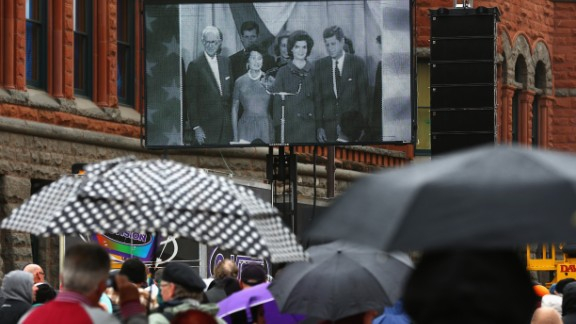 People near Dealey Plaza watch a historical broadcast about Kennedy's life.