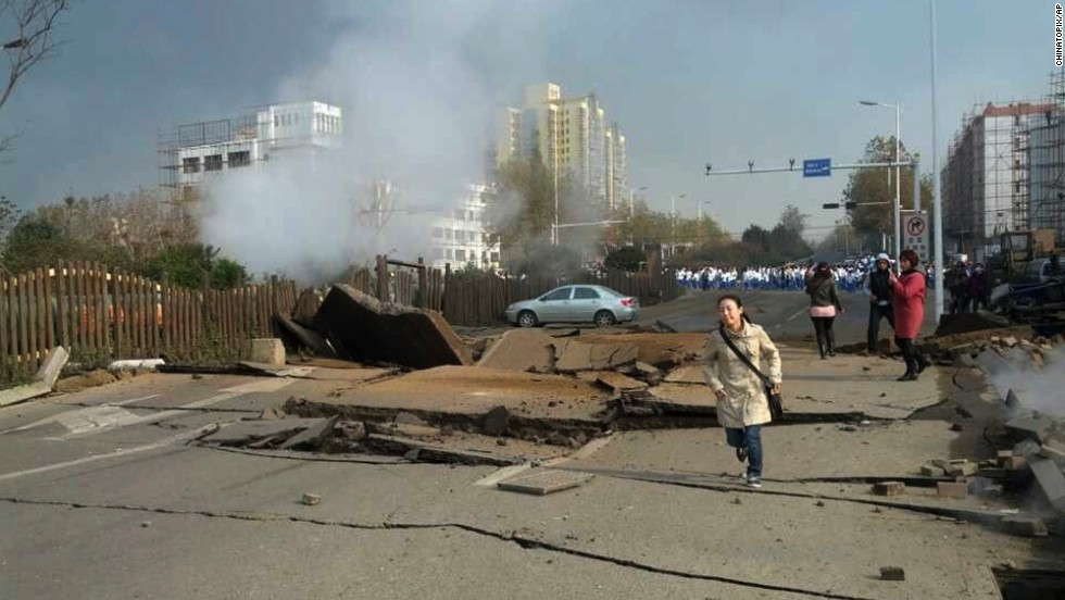A woman runs down a damaged street following the explosion November 22.