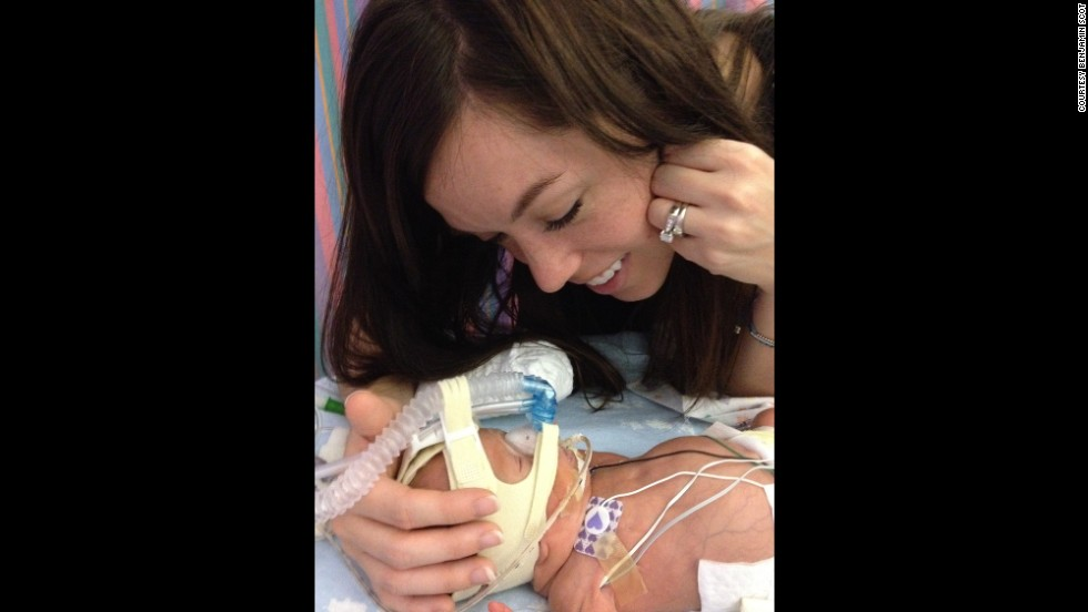 Lyndsey Miller looks adoringly at her son in the NICU while she cradles his tiny head surrounded by tubes and wires.