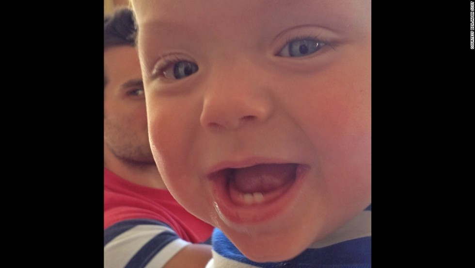 Ward gives a big gummy smile to the camera. His dad keeps a close eye on his son from behind.