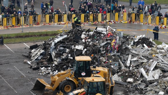 Debris piles up while people put flowers and light candles in front of the supermarket on November 23. The collapse was the Baltic state