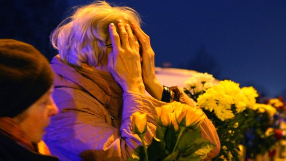 People leave flowers at the scene where the supermarket roof collapsed in Riga on Friday, November 22.