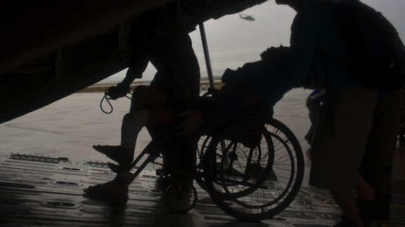 A sick elderly man is wheeled onto a Philippines military cargo aircraft as he and fellow survivors of  the typhoon are evacuated from Tacloban to Manila on November 23.