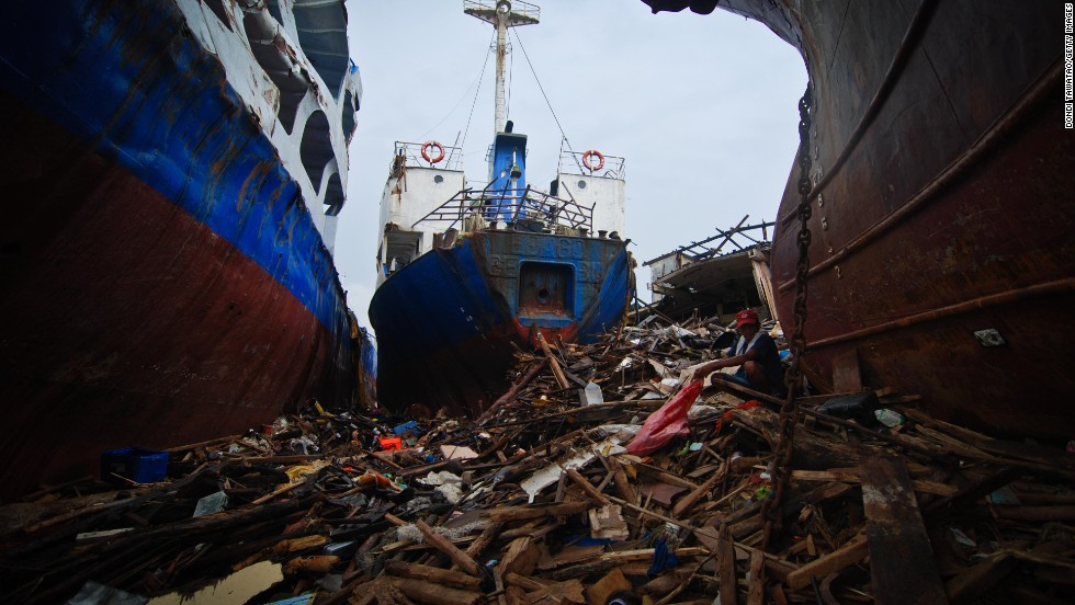 A man scavenges piles of wood amid damaged container vessels on November 23 in Tacloban.