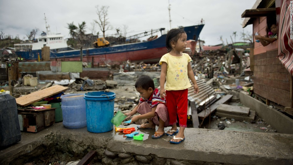 A young boy cleans salvaged toys near a ship that was washed ashore by Super Typhoon Haiyan in this Tacloban, Philippines, on November 23, 2013.