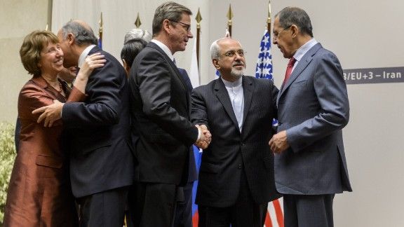 EU foreign policy chief Catherine Ashton and French Foreign Minister Laurent Fabius share a hug while German Foreign Minister Guido Westerwelle, Iranian Foreign Minister Mohammad Javad Zarif and Russian Foreign Minister Sergei Lavrov talk.