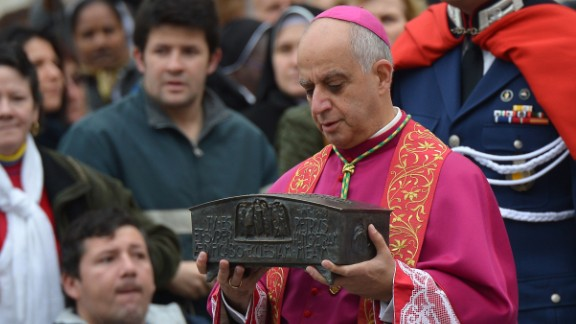 Italian archbishop Rino Fisichella holds the ashes of St Peter before a ceremony of Solemnity of Our Lord Jesus Christ the King at St Peter
