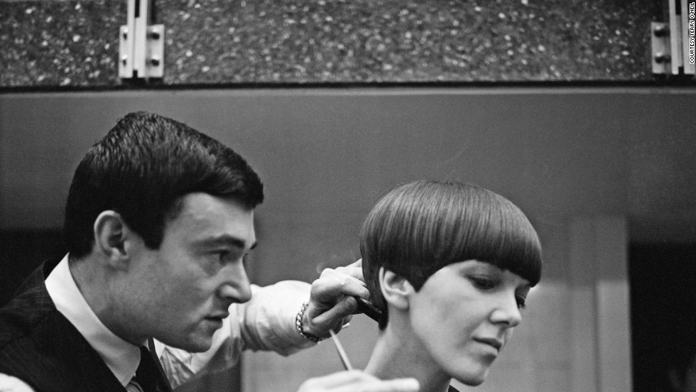 "Legendary hairdresser Vidal Sassoon applies the finishing touches of his trademark ""wedge bob cut"" to miniskirt inventor Mary Quant. ""I was walking down Bond Street and there was a picture of a haircut that knocked me sideways. I knew I wanted <em>my </em>hair cut like <em>that,"" </em>says Quant."