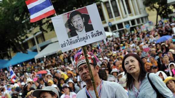 A Thai opposition protester holds up a placard mocking exiled former leader, Thaksin Shinawatra. Thaksin has a strong support base among Thailand