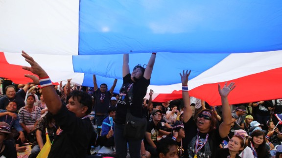 Anti-government protesters ripple a giant Thai flag.