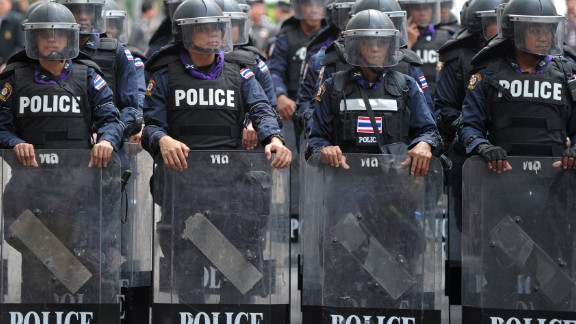 Thai riot police stand guard in Bangkok on Monday in an escalation of mass street rallies aiming to topple Prime Minister Yingluck Shinawatra