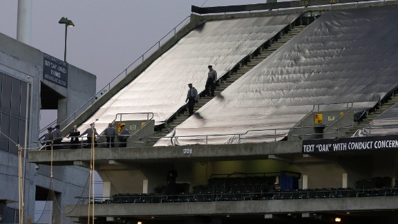 Law enforcement officials walk in the upper deck of O.co Coliseum after an NFL football game between the Oakland Raiders and the Tennessee Titans.