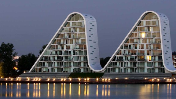 The Wave building in the Danish town of Vejle mirrors the soft movements on the surface of the fjord during the day and resembles illuminated mountain peaks at night.