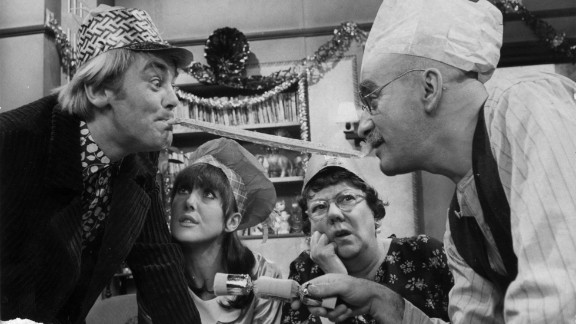 """Alf Garnett (Warren Mitchel) and son-in-law Mike (Anthony Booth) argue during Christmas dinner in the BBC's """"Till Death Do Us Part."""""""