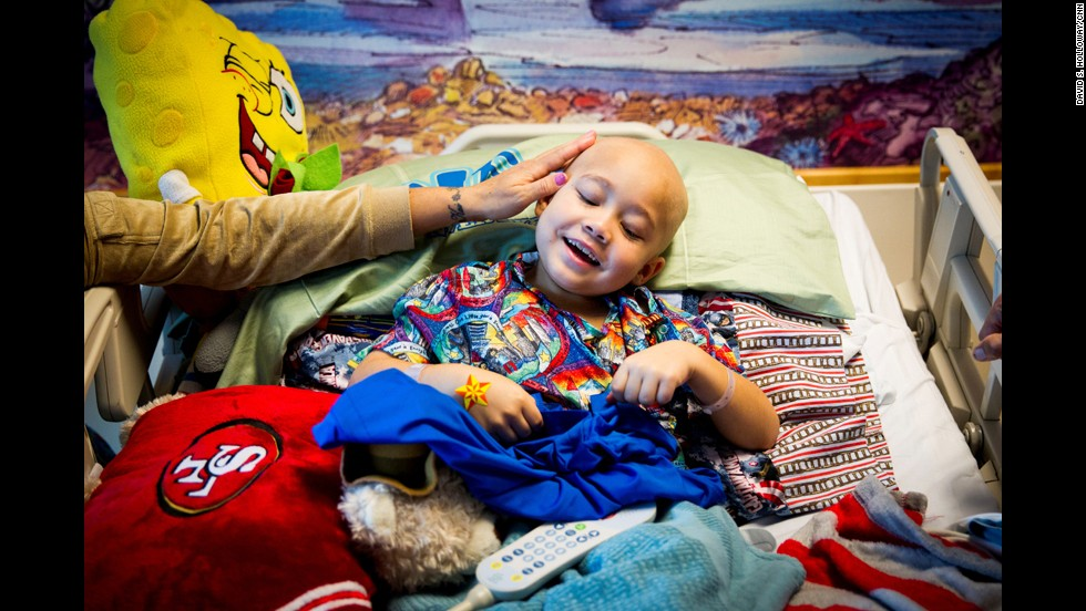 "A young patient holds his ""Loving Tabs"" T-shirt."