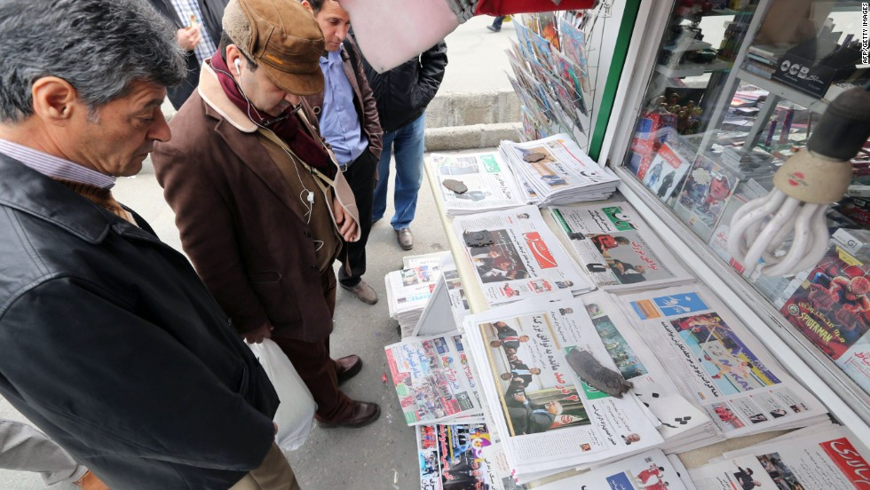 Iranians look at newspapers displayed outside a kiosk on November 24, 2013 in Tehran a day after a deal was reached on the country's nuclear program.