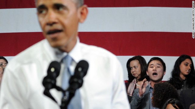 An attendee (back, 2nd R) heckles US President Barack Obama as he speaks on immigration reform at Betty Ann Ong Chinese Recreation Center in San Francisco, California, on November 25, 2013.