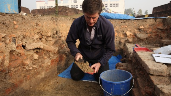 Coningham works in the trench in the remains of an ancient monastery. The Maya Devi Temple is in the background.