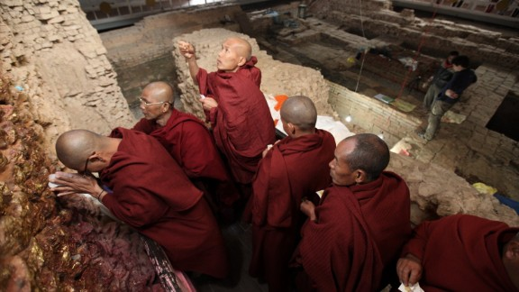 Pilgrims meditate at the Maya Devi Temple, with ancient remains in the background, at Lumbini in Nepal. The site is said to be the birthplace of the Buddha.