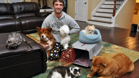 Keith Piasecki poses for his family's 2013 Christmas card newsletter with, clockwise from left, Tiki, Cayenne, Sneaky Poof, Prescious, Freddy Mercury and Joon. Squint hard and you can see Bert and Ernie, the clown fish, in the tank behind Piasecki's head.