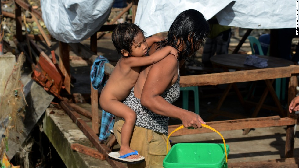 A mother carries her baby through the debris of destroyed houses in Tacloban, Leyte province, Philippines on Wednesday, November 27, 2013  Typhoon Haiyan, one of the strongest storms in recorded history, has devastated parts of the Philippines and killed thousands of people.