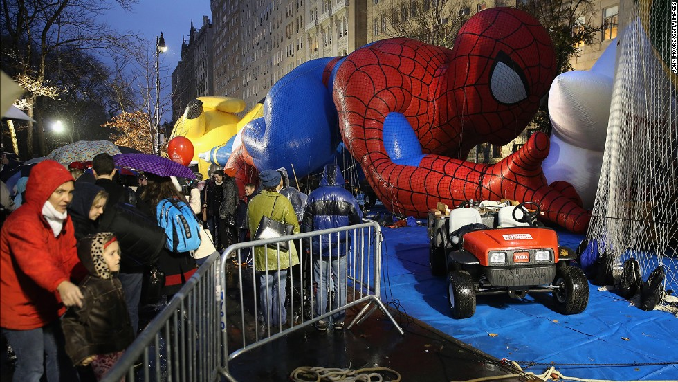 Sightseers photograph the balloons, including Spiderman and Pikachu, on the night before the parade.