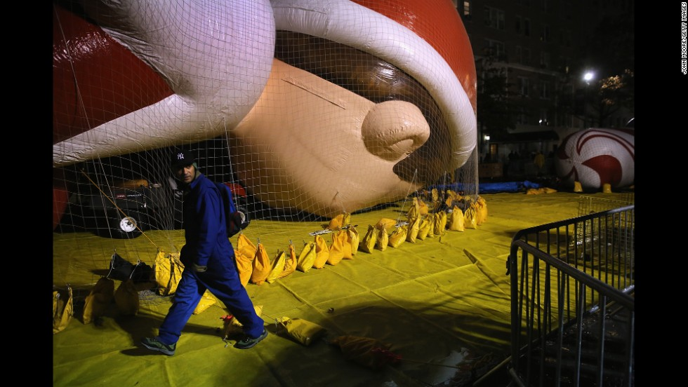 Sandbags hold the Elf on a Shelf balloon down as workers prepare in hopes the balloons will get to fly.