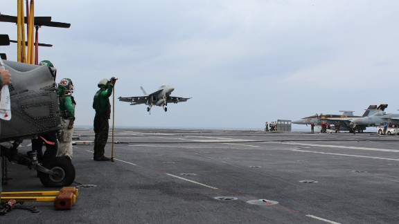 The carrier's air wing carry out launch and recovery operations night and day -- an FA-18 on final approach ...
