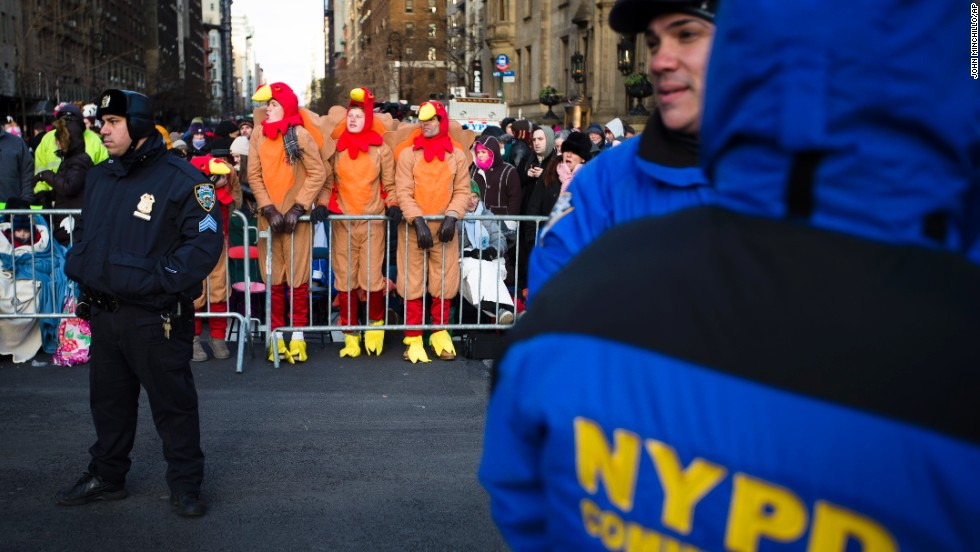 Spectators stand behind police barricades as they wait for the parade to start.