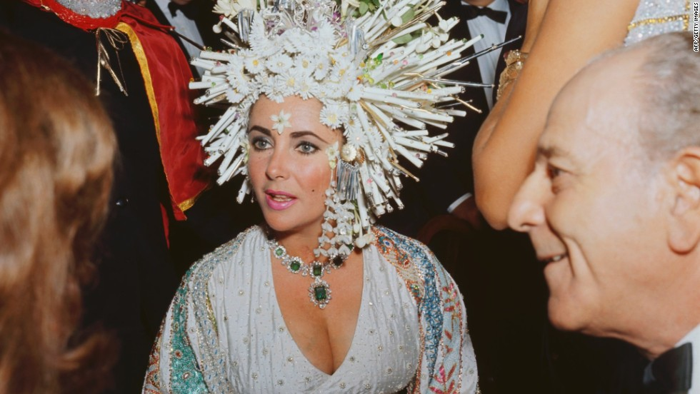 Elizabeth Taylor was famous for wearing flamboyant jewelry, and her collection featured some extremely valuable pieces. Here she is wearing an elaborate headdress of pearls and fake flowers, but her emerald necklace still stands out.