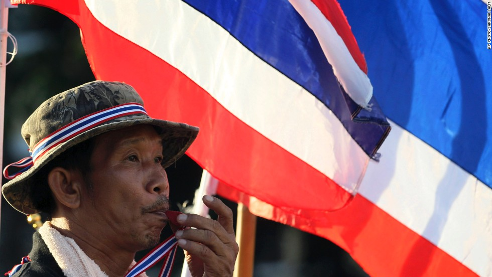 An anti-government protester blows a whistle in front of Thai flags during a rally at Bangkok's Democracy Monument on Friday, one day after the embattled Prime Minister Yingluck Shinawatra survived a no-confidence vote in parliament.