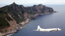 A Japanese military plane flies over the Senakuku / Diaoyu Islands in this photo.