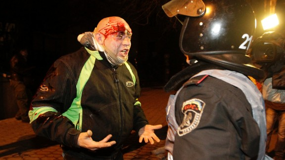 A bleeding protester shouts at a police medic after police pushed protesters off the street leading to the presidential administration building on December 1.