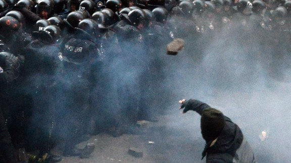 A Ukrainian protester throws stones at riot police during clashes outside the president