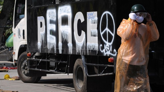 """An anti-government protester walks past a police vehicle with the word """"peace"""" painted where """"police"""" used to be."""
