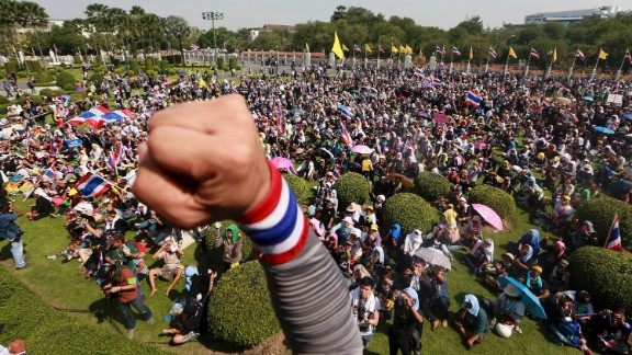 An anti-government protester raises his fist after entering the compound of Government House in Bangkok, Thailand, on Tuesday, December 3. Police removed barricades and allowed demonstrators to enter the government compound as well as the metropolitan police office as part of a truce between protesters and the Thai government for the next few days.