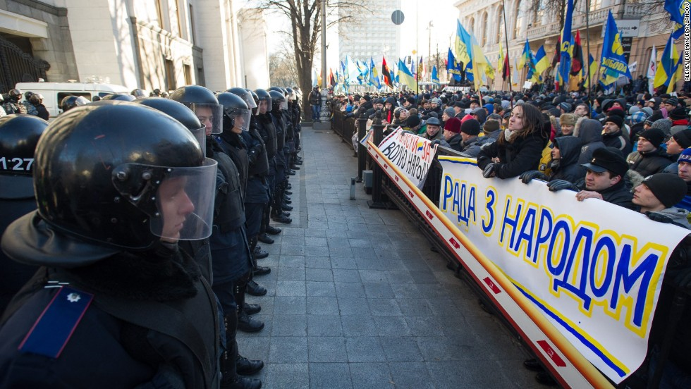 Police stand guard opposite a sea of protesters near the Ukrainian parliament in Kiev on December 3.