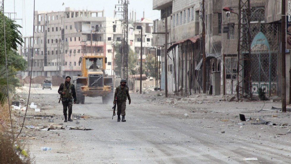 Syrian troops patrol the deserted streets of Sbeineh, south of Damascus, on November 8 after retaking the suburb from rebel forces.