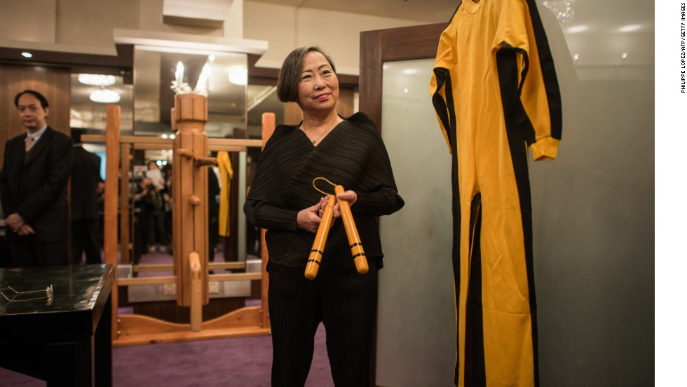 "Spink auction house vice chairperson, Anna Lee, presents a yellow and black jumpsuit worn by Bruce Lee and his nunchaku used during the filming of ""Game of Death"" in 1972."
