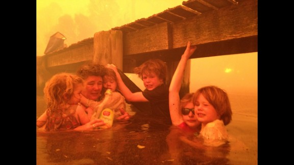 January 4: Tammy Holmes and her grandchildren take refuge under a jetty as a wildfire rages nearby in the Tasmanian town of Dunalley, Australia.