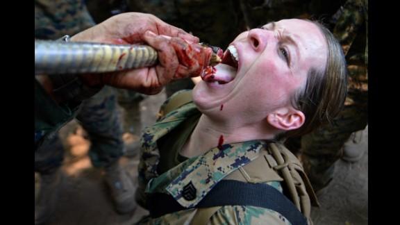 February 20: A U.S. Marine drinks cobra blood during a jungle survival program at a base in Sattahip, Thailand.