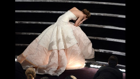 """February 24: Actress Jennifer Lawrence falls during the Academy Awards as she walks up stairs to receive the Best Actress Oscar for """"Silver Linings Playbook."""""""