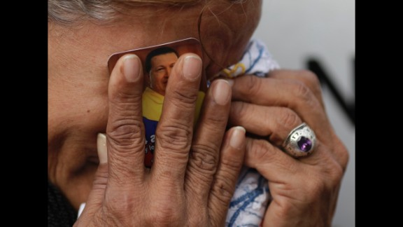 March 6: A crying woman holds a picture of Venezuelan President Hugo Chavez outside the military hospital where he died one day earlier in Caracas, Venezuela. Chavez, who had battled cancer, was 58.
