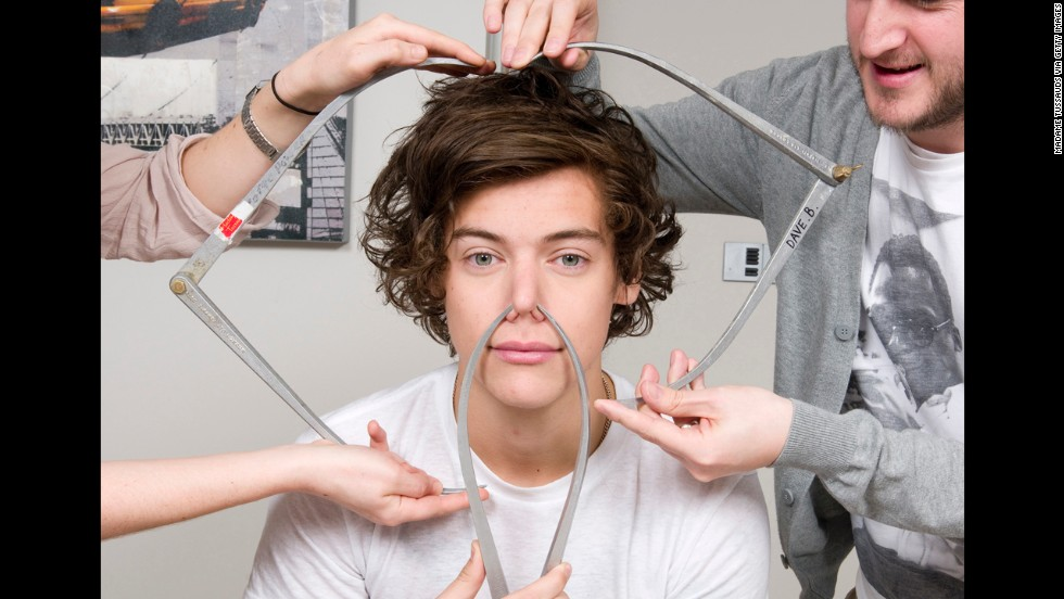 <strong>March 11:</strong> Harry Styles of the boy band One Direction poses with calipers as he is measured for a wax figure by Madame Tussauds.