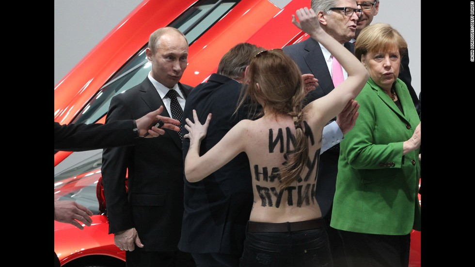 <strong>April 8:</strong> Russian President Vladimir Putin is attacked by an activist of the Ukrainian women rights group Femen as German Chancellor Angela Merkel looks on in Hannover, Germany.