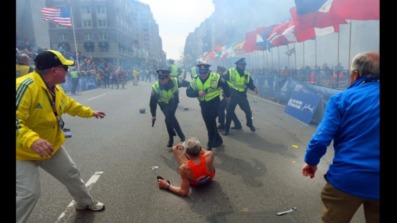 April 15: Police officers stand over marathon runner Bill Iffrig as a second explosion sounds near the finish line of the Boston Marathon. Three people were killed and at least 264 were injured in the terror attack.