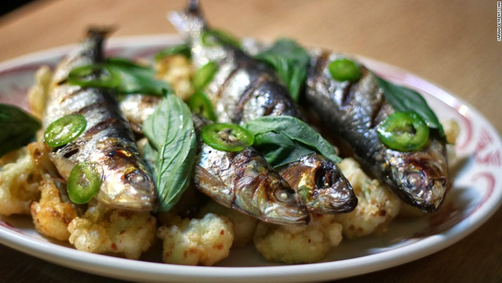 To serve, create a family style platter with the cauliflower florets on the bottom and the sardines on top. Whisk the juice from a lemon with 3 tablespoons of olive oil and 15-20 jalapeno slices. Drizzle over everything and top with basil leaves.
