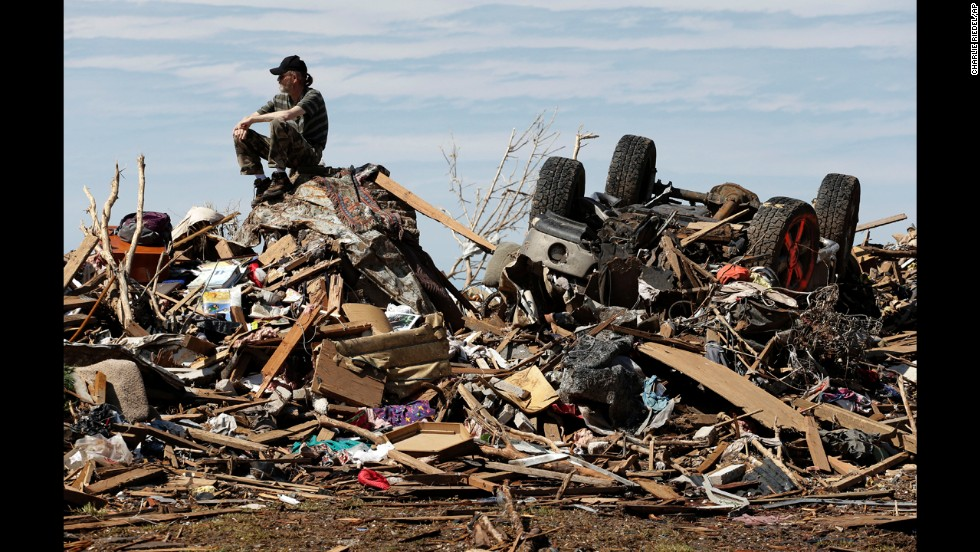 <strong>May 23:</strong> David Lee Estep waits for his parents on a pile of rubble that used to be their home in Moore, Oklahoma. Moore was hit by a massive EF5 tornado that killed 24 people, including seven students at an elementary school.