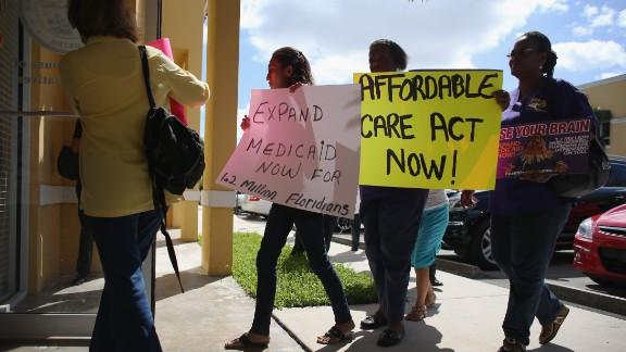 Demonstrators walk into a Florida state legislator