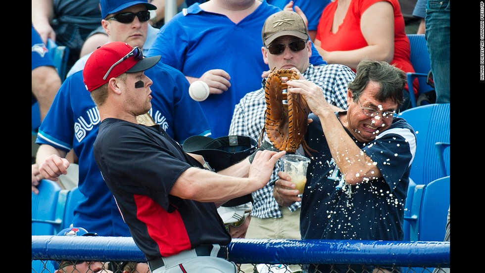 Minnesota Twins first baseman Justin Morneau, left, spills a fan's beer while chasing a foul ball during the first inning of an exhibition spring training game against the Toronto Blue Jays in Dunedin, Florida, on February 26.
